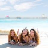 说谎在海滩的愉快的三个朋友女孩铺沙smil 免版税库存照片