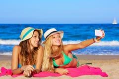 说谎在海滩的愉快的女朋友selfie画象 免版税库存图片