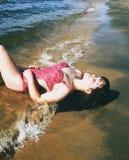 说谎在海滩的桃红色泳装的妇女 免版税库存照片