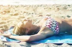 说谎在海滩的比基尼泳装的白肤金发的妇女 库存照片