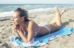 说谎在海滩的比基尼泳装的美丽的白肤金发的妇女 免版税库存图片