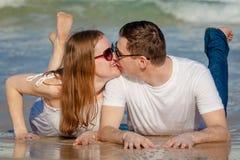 说谎在海滩的爱恋的夫妇在天时间 免版税库存图片