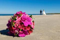 说谎在海滩的美丽的新娘花束 免版税库存图片
