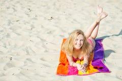 说谎在海滩的美丽的年轻白肤金发的妇女 免版税图库摄影