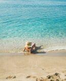 说谎在清楚的海水的比基尼泳装的资深妇女游人 免版税库存图片
