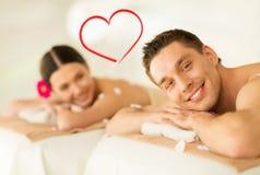 说谎在温泉沙龙的按摩桌上的微笑的夫妇 库存图片