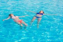 说谎在游泳池的两名美丽的妇女浇灌表面 库存图片