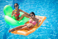 说谎在游泳池的气垫的两个女孩 免版税库存照片