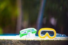 说谎在游泳池附近的两个湿水肺面具 库存图片