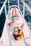 说谎在游艇甲板的女孩 泳装的微笑的夫人 放松并且享受您的假期 在海中的异乎寻常的地方 图库摄影