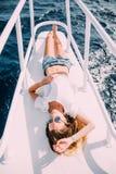 说谎在游艇甲板的女孩 泳装的微笑的夫人 放松并且享受您的假期 在海中的异乎寻常的地方 免版税库存图片