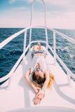说谎在游艇甲板的女孩 泳装的微笑的夫人 放松并且享受您的假期 图库摄影
