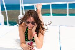说谎在游艇的甲板的泳装的妇女和采取sel 免版税库存照片