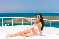 说谎在游艇的甲板的白色泳装的女性在太阳 免版税图库摄影