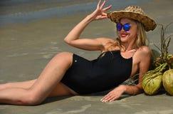 说谎在热带海滩的妇女戴黑享受她的假期的泳装和帽子 库存照片