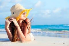 说谎在热带的比基尼泳装和草帽的妇女 免版税库存图片