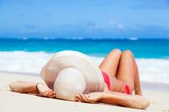 说谎在热带的比基尼泳装和草帽的妇女 免版税图库摄影