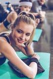 说谎在瑜伽席子和看去,当行使健身房时的年轻女运动员 免版税图库摄影