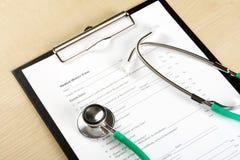 说谎在病历(病史)的绿色听诊器的医疗概念 库存图片