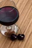 说谎在白兰地酒杯的两棵樱桃汁液附近 图库摄影