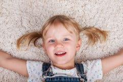 说谎在白色地毯的微笑的逗人喜爱的孩子女孩和 免版税库存图片