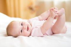 说谎在白色床上和握她的腿的女婴 免版税库存照片