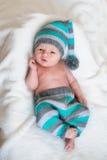 说谎在白色床上的一个被编织的帽子的小男婴 免版税库存照片