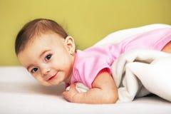 说谎在白色毛巾的愉快的婴孩 免版税库存图片