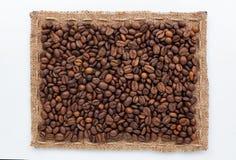 说谎在白色背景的粗麻布和咖啡豆框架  免版税库存图片