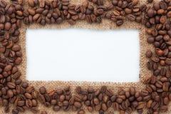 说谎在白色背景的粗麻布和咖啡豆框架  图库摄影