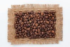 说谎在白色背景的粗麻布和咖啡豆框架  免版税图库摄影
