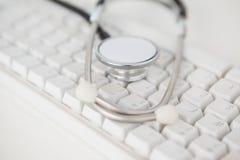 说谎在白色键盘的听诊器 免版税库存图片
