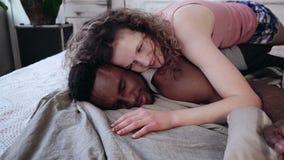 说谎在睡衣的人的年轻美丽的妇女 拥抱在床上的多种族夫妇,举行手和微笑 影视素材