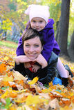 说谎在秋叶中的母亲和小女儿 库存图片