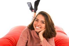 说谎在红场的微笑的俏丽的妇女塑造了装豆子小布袋沙发iso 免版税库存照片