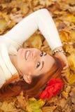 说谎在红色叶子中的少妇 库存图片