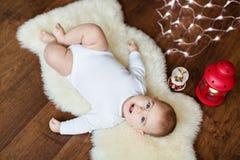 说谎在背景光的白色皮肤的小逗人喜爱的婴孩 免版税库存照片