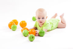 说谎在背景和微笑在果子中的婴孩 免版税库存图片