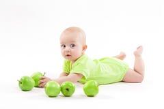 说谎在背景和微笑的逗人喜爱的婴孩 免版税库存照片