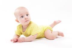 说谎在背景和微笑的逗人喜爱的婴孩 免版税库存图片