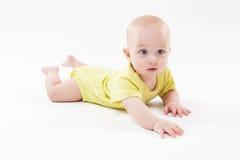 说谎在背景和微笑的逗人喜爱的婴孩 图库摄影