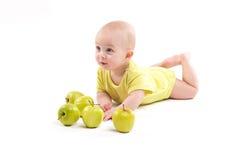 说谎在背景的微笑的婴孩包括苹果 免版税库存图片