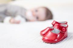 说谎在背景的婴孩红色鞋子和宝贝 库存图片