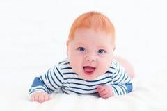 说谎在腹部的愉快的红头发人男婴画象  库存照片