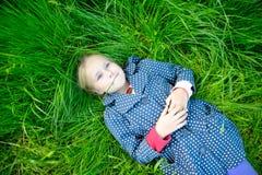 说谎在草和作的小白肤金发的女孩 库存图片