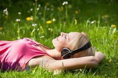 说谎在草和听到与耳机的音乐的少妇 免版税库存图片
