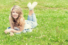 说谎在草和微笑的愉快的年轻美丽的性感的女孩在牛仔裤在一个晴朗的夏日在庭院里 免版税库存照片
