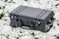 说谎在草和雪的塑料黑保护者盒 库存照片