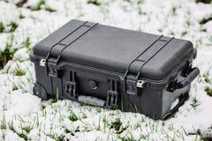 说谎在草和雪的塑料黑保护者盒 免版税库存照片