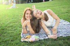 说谎在草坪的两个朋友 库存图片